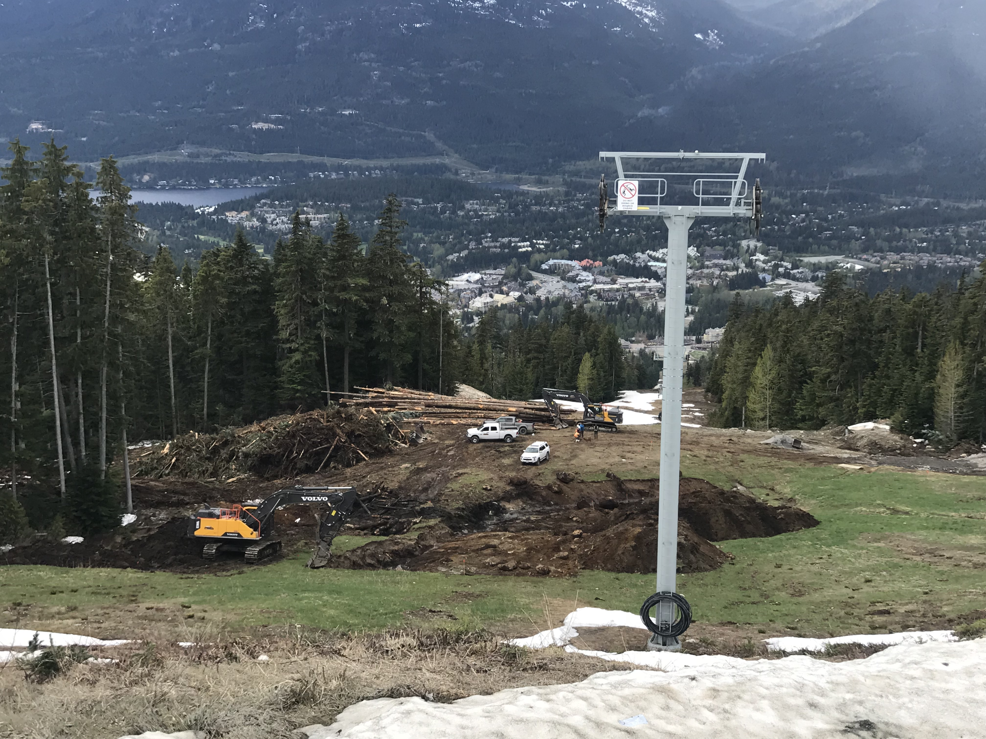 ground being cleared on ski slope with views of Whistler Village